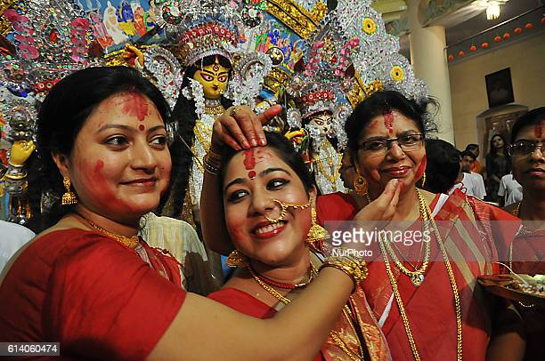 Hindu women apply sindhur or vermillion powder on each others face after worshipping the idol of the Hindu goddess Durga on the last day of the Durga...