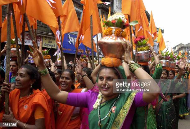 Hindu women devotees carry brass pots as as they walk to make an offering in the River Godavari on the first day of the monthlong 'Kumbh Mela...