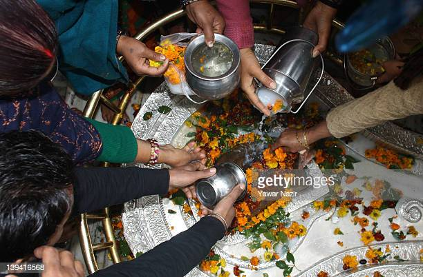 Hindu women devotees pour sacred water and milk as prayer on the idol of Lord Shiva's lingam during the Mahashivratri festival on February 20 2012 in...