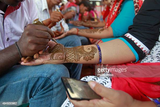 Hindu women getting henna tattoos on their arms during the eve of Karva Chauth Festival at a road side shop