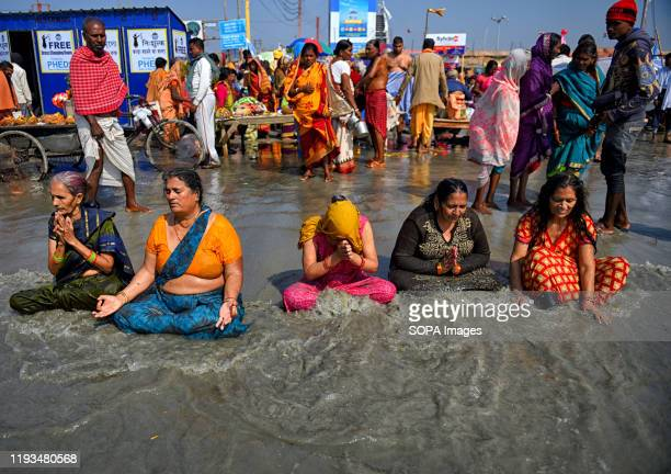 Hindu women pilgrims take a Holy Bath at Gangasagar during the Makar Sankranti Transition as per ritual. Gangasagar is one of the religious spot for...