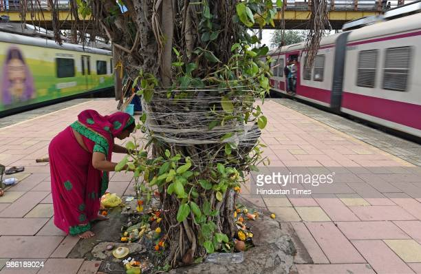 Hindu women tying threads and performing puja around the holy Banyan tree on the occasion of Vat Purnima at Jogeshwari Railway Station on June 27...