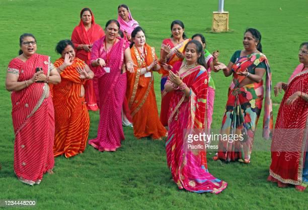 Hindu women wearing colorful lahariya saris, perform dance as they celebrate the holy month of Sawan in Beawar.