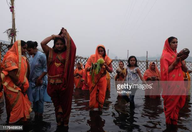 Hindu women worship the Sun god on the banks of Yamuna River during the celebrations of the Hindu religious festival Chhath Puja on a smoggy evening...