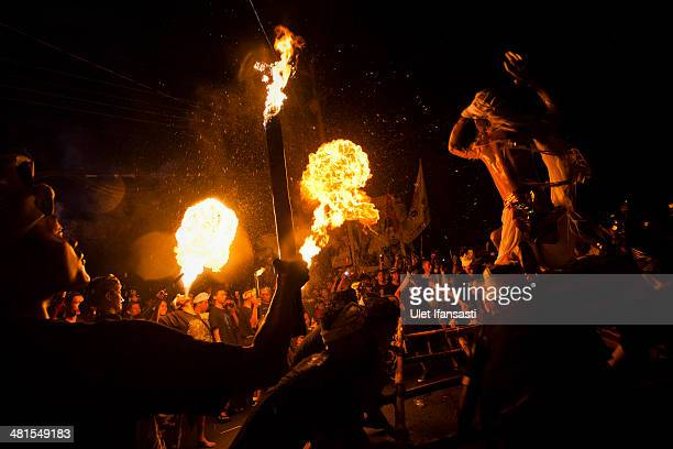 Hindus devotees breath fire as they carry a effigy known as 'OgohOgoh' during a parade on March 30 2014 in Yogyakarta Indonesia Balinese Hindus hold...