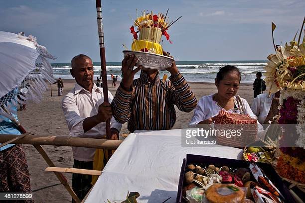 Hindus devotees carry offerings during the Melasti ritual ceremony at Parangkusumo beach on March 28 2014 in Yogyakarta IndonesiaThe Melasti ritual...