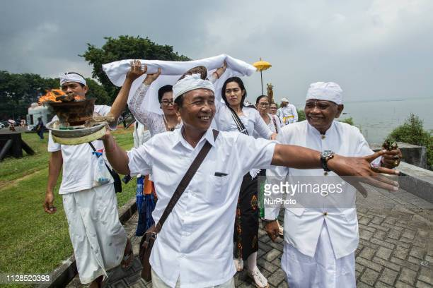 Hindus devotees pray during the Melasti ritual ceremony at Arafuru beach on March 03 2019 in Surabaya East Java Indonesia The Melasti ritual is held...