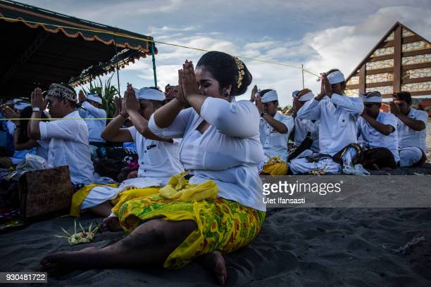 Hindus devotees pray during the Melasti ritual ceremony at Parangkusumo beach on March 11 2018 in Yogyakarta IndonesiaThe Melasti ritual is held...