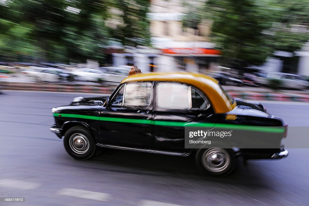 A Hindustan Motors Ltd. Ambassador taxi drives along a road in New Delhi, India, on Saturday, Sept. 19, 2015. As cabs lured by app-based platforms proliferate in India, where car ownership is low and public transportation services in most cities and towns havent kept pace with the needs of a growing population, drivers are facing stiffer competition for rides. Photographer: Dhiraj Singh/Bloomberg via Getty Images