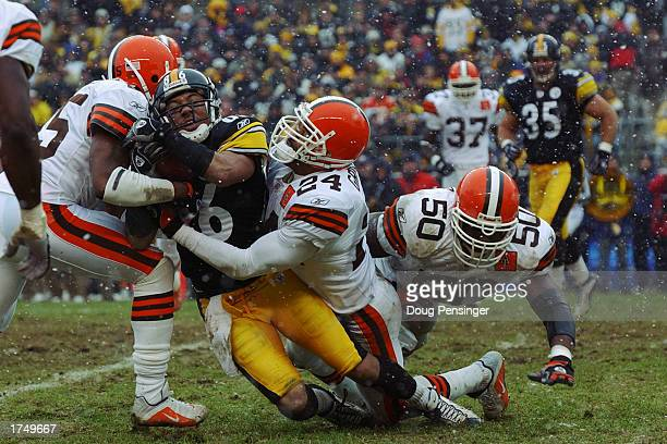 Hines Ward of the Pittsburgh Steelers is tackled by Robert Griffith and Corey Fuller of the Cleveland Browns during an AFC Wild Card game at Heinz...