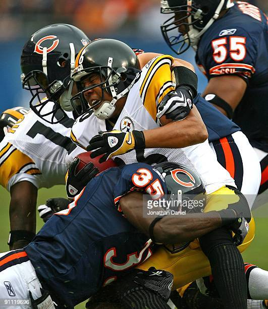 Hines Ward of the Pittsburgh Steelers is tackled by Zackary Bowman of the Chicago Bears as teammate Hunter Hillenmeyer pushes Santonio Holmes away on...