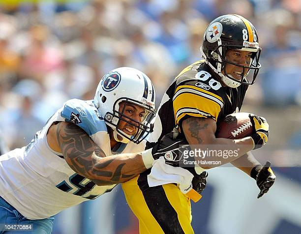 Hines Ward of the Pittsburgh Steelers makes a catch under pressure from Jason Babin of the Tennessee Titans during the first half at LP Field on...
