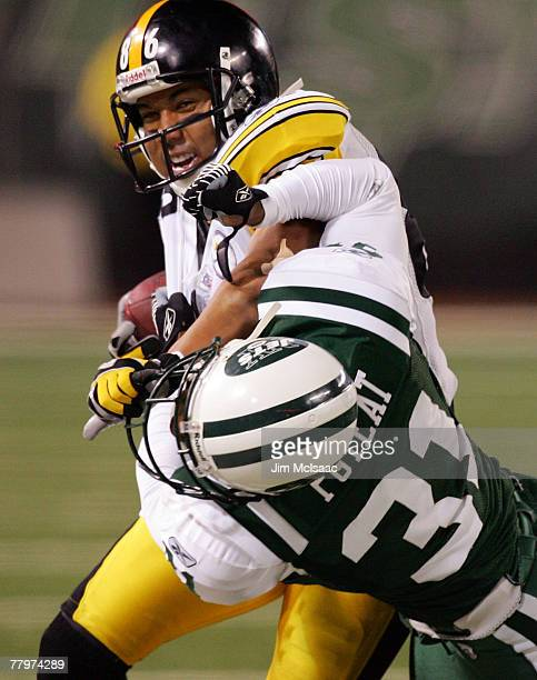Hines Ward of the Pittsburgh Steelers runs the ball against Hank Poteat of the New York Jets at Giants Stadium November 18 2007 in East Rutherford...