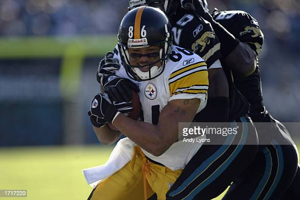 Hines Ward of the Pittsburgh Steelers runs with the ball while tackled by Fernando Bryant and Wali Rainer of the Jacksonville Jaguars during the NFL...