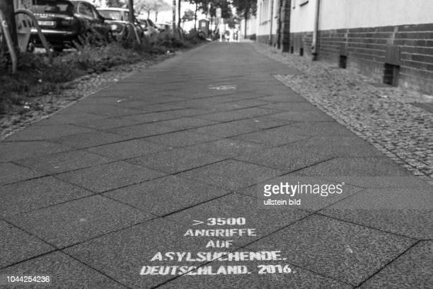 Hinweis zu der Anzahl von Angriffen auf Geflüchtete und Asylsuchende in Deutschland als Graffito auf einem Gehweg in Berlin-Prenzlauer Berg