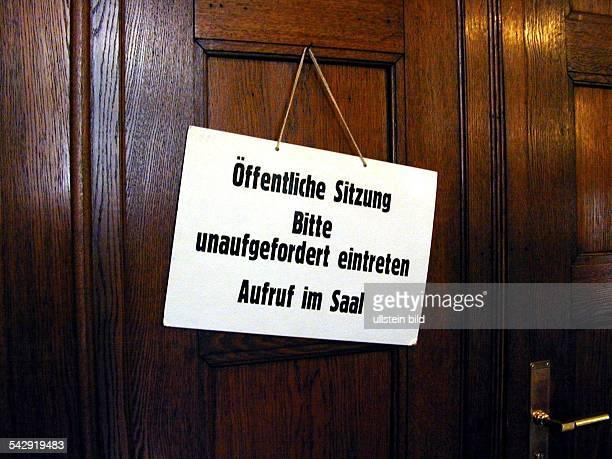 Hinweisschild einer öffentlichen Sitzung an der Tür eines Gerichtssaals im Ziviljustizgebäude Das Schild trägt den Text Öffentliche Sitzung Bitte...