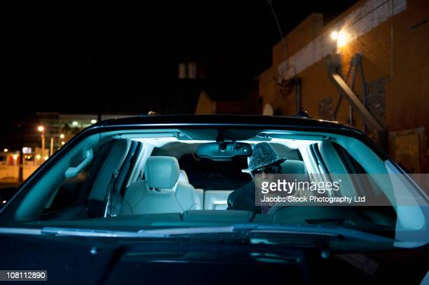 Hip African American man driving car at night