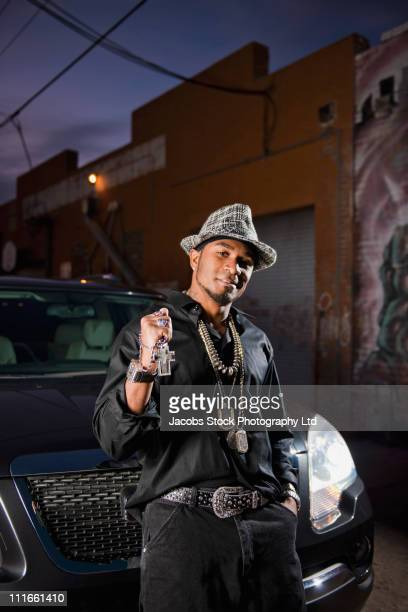hip african american man holding cross necklace near car - pimped car stock photos and pictures