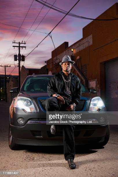 hip african american man leaning on car hood - pimped car stock photos and pictures