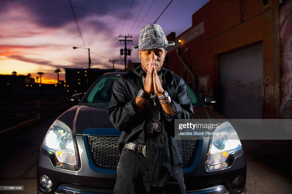 Hip African American man praying near car at night : Stock Photo