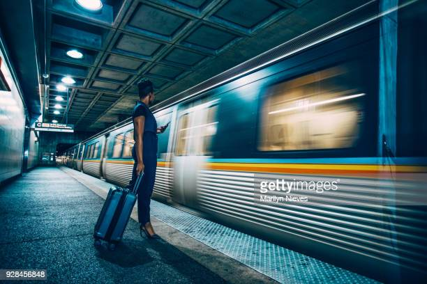 hip confident black businesswoman and a train arriving - railroad stock photos and pictures