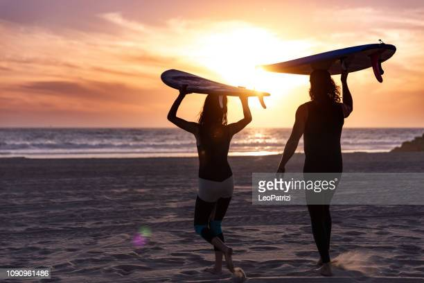 hip couple in venice going to surf in the pacific ocean - venice foto e immagini stock