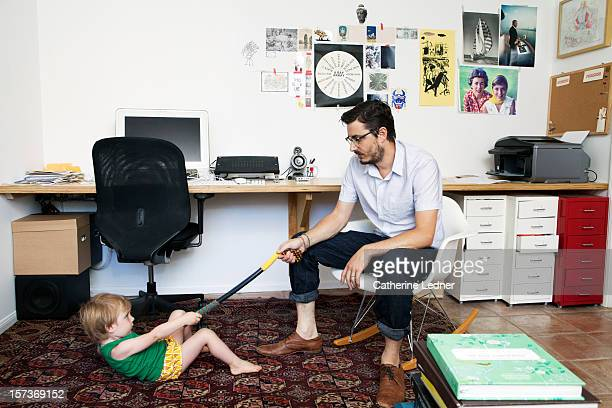 Hip father playing with toddler in home office