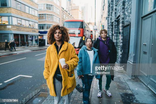 hip friends walking in the city - mode of transport stock pictures, royalty-free photos & images