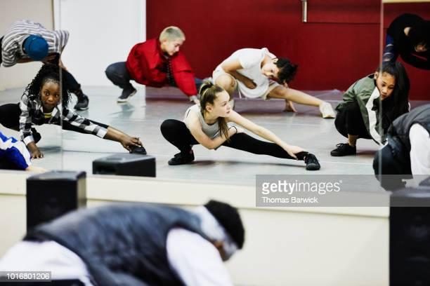hip hop dance group stretching in dance studio before practice - dance troupe bildbanksfoton och bilder