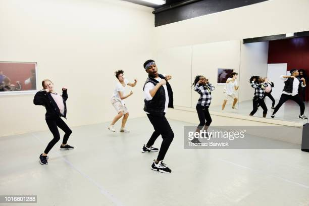 hip hop dance instructor leading practice with students in dance studio - dance troupe stock photos and pictures