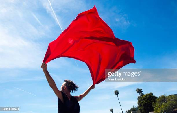 hip man holding onto red fabric flag against blue sky - flag stock pictures, royalty-free photos & images