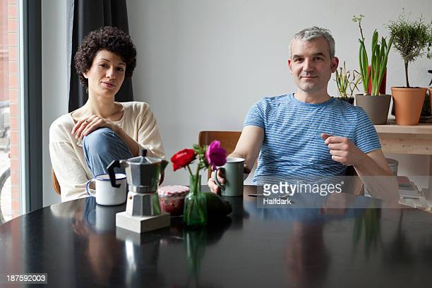 A hip mixed age couple having breakfast in their modern dining table