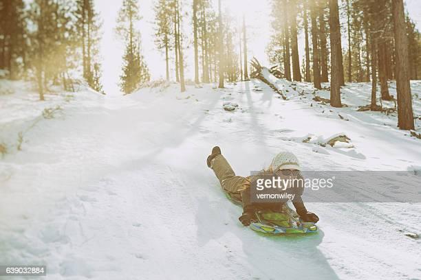 Hip mom sleds down steep hill