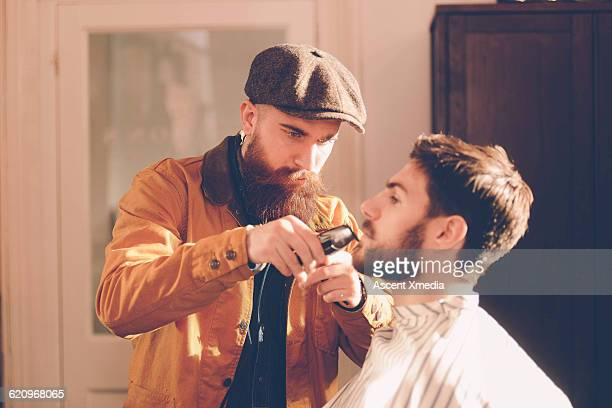 Hip stylist trims customer's beard in barber shop