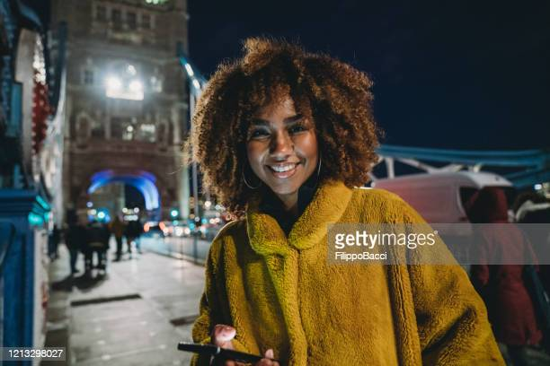 hip young adult woman using her smartphone in the city on tower bridge - teenager stock pictures, royalty-free photos & images