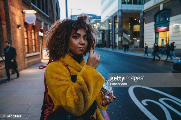 hip young adult woman waiting for a ride in london - street style stock pictures, royalty-free photos & images