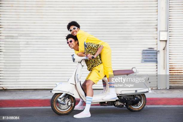 a hip young couple on a scooter - friendship stock pictures, royalty-free photos & images