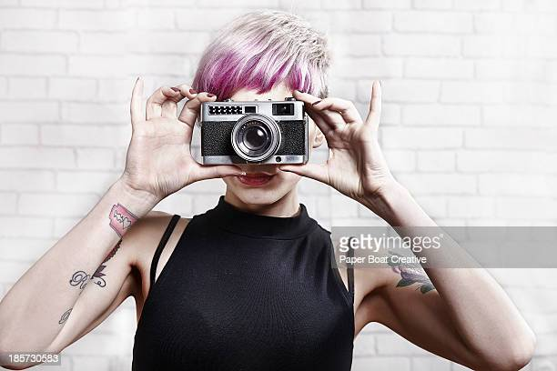 Hip young lady taking a photo with her film camera