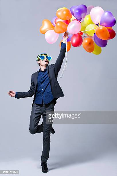 hip young man with balloons - flying solo after party bildbanksfoton och bilder