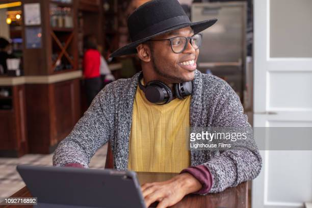 hip young man with digital tablet in airport bar smiles as he looks out the window. - black hat stock pictures, royalty-free photos & images