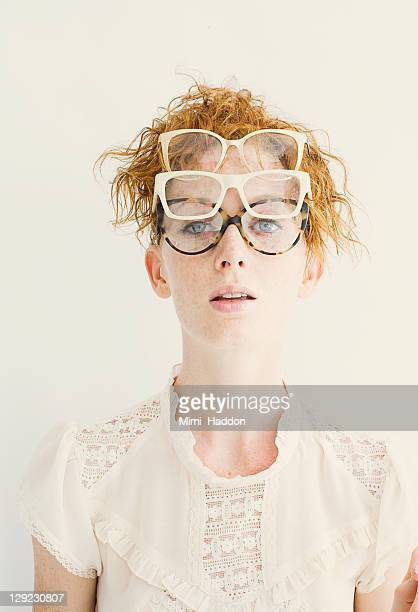 hip young woman wearing multiple pairs of glasses - lace blouse stock pictures, royalty-free photos & images
