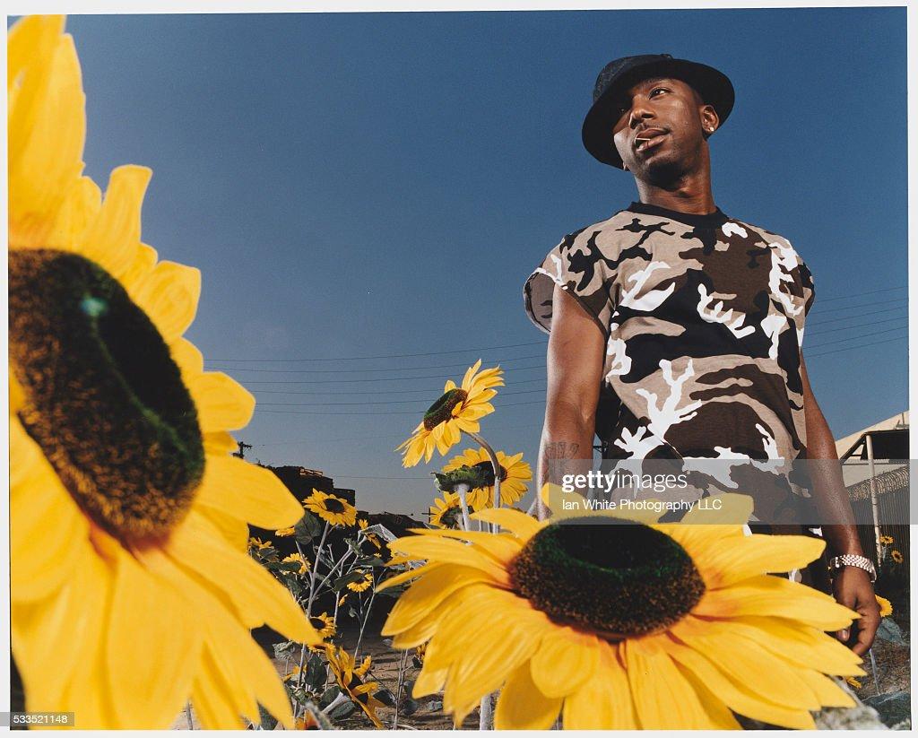 Hip-Hop Artist Ras Kass with Sunflowers : News Photo