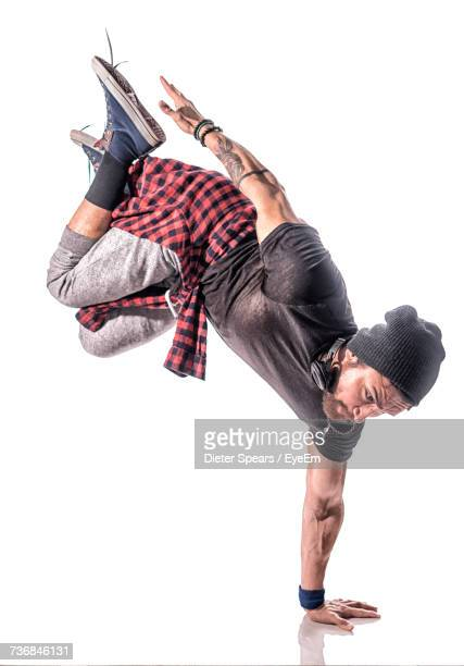 hip-hop dancer doing handstand against white background - breakdancing stock photos and pictures