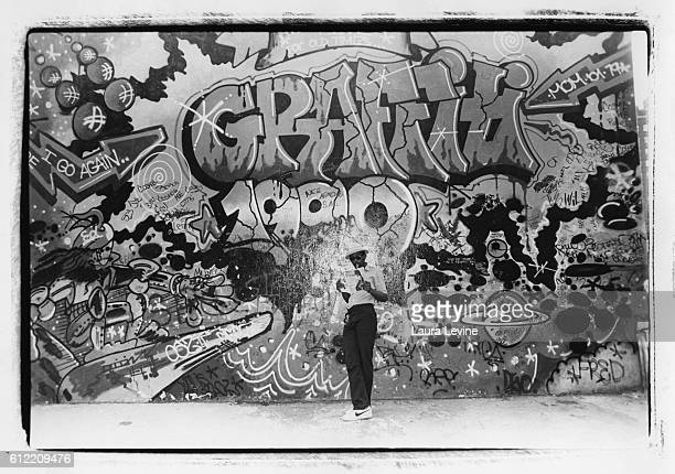 Hiphop personality Fab Five Freddy in front of a Lee Quinones grafitti mural in Lower Manhattan on Monroe Street in the Lower East Side