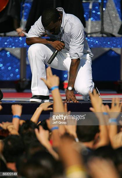 HipHop recording artist Kanye West kneels down and bows his head as he performs during a free concert to celebrate the Opening Kickoff of the 200506...