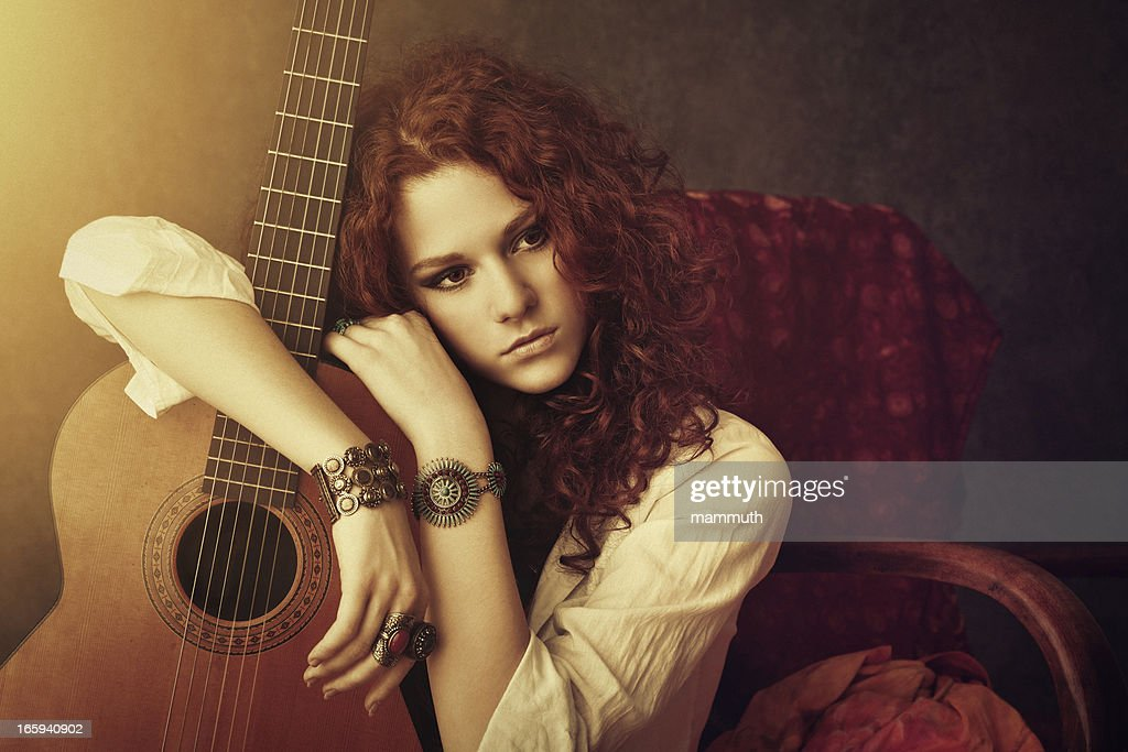 hippie girl embracing her acoustic guitar : Stock Photo