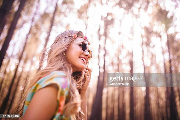 Hippie girl in boho fahion in a bright forest