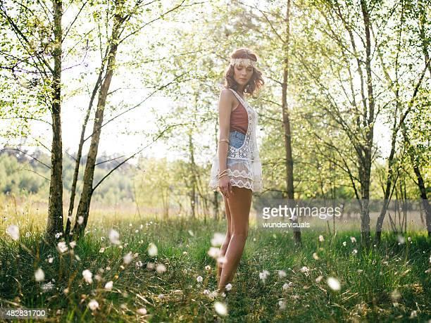 Hippie girl looking back in einem Sommer-park mit Blumen