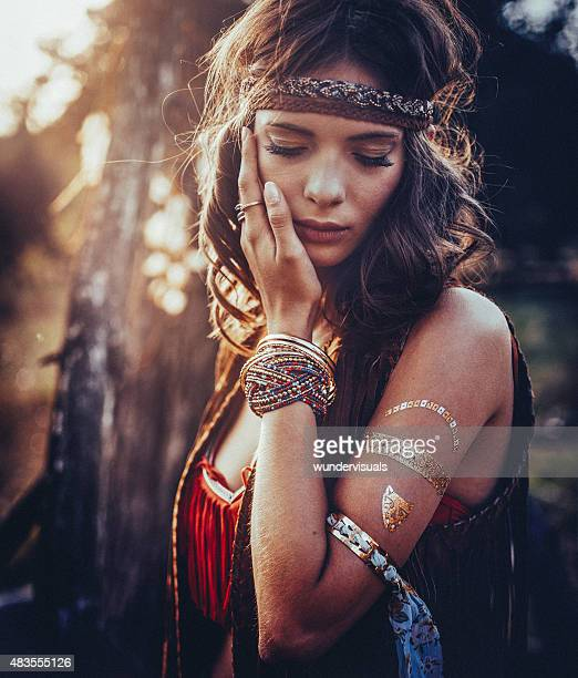 hippie girl outdoors with jewelry and temporary gold foil tattoo - hippie woman stock photos and pictures