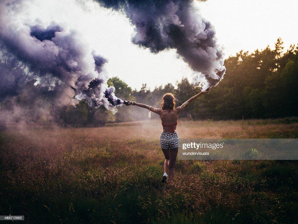 Hippie girl running through field with purple smoke flares : Stock Photo